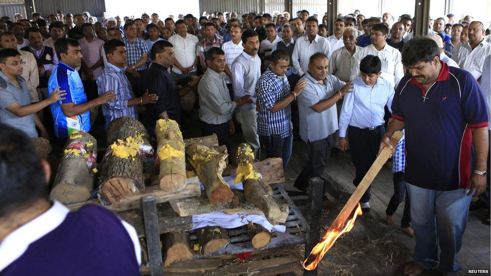 The father (R) of Nehal Vekaria, a 16-year-old female student who was killed during the Westgate Shopping Centre, holds a stick lit with fire at her cremation ceremony in Nairobi (22 September 2013)