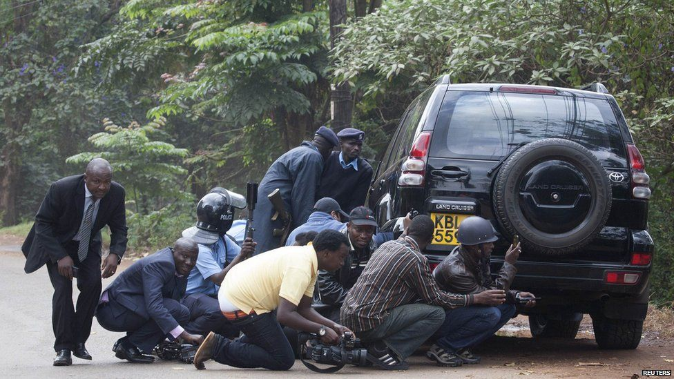 Police officers and members of the media take cover at a distance from the Westgate Shopping Centre after continuous gunfire was heard on September 23, 2013.