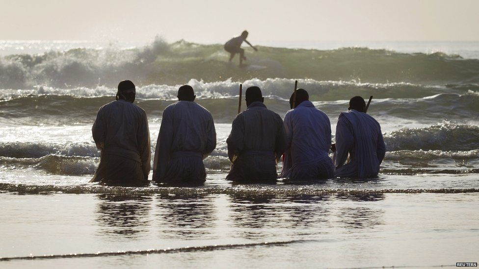 Members of South Africa's Shembe Church kneeling in water on a beach in Durban, South Africa - Saturday 5 October 2013