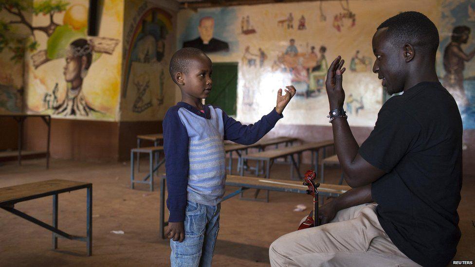 A boy learning to hold a violin, Nairobi, Kenya - Sunday 6 October 2013