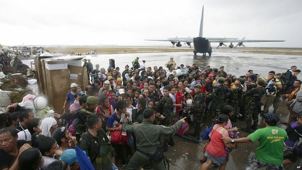 Typhoon survivors rush to get a chance to board a C-130 military transport plane out of Tacloban city, Leyte province, central Philippines
