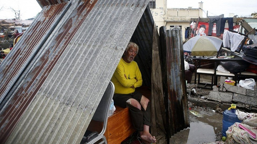 A man made homeless by Typhoon Haiyan sits at a makeshift shelter along a road in Palo, Leyte