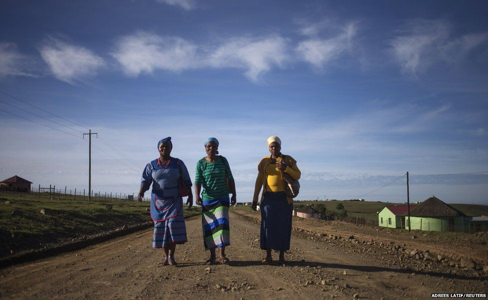 Villagers walk by foot on a dirt road to a public viewing point near the ancestral home of former South African President Nelson Mandela, to take part in his funeral ceremony in Qunu