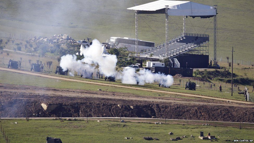 South African National Defence Forces fire ceremonial cannons as the body of Nelson Mandela is brought from the family home to the funeral tent