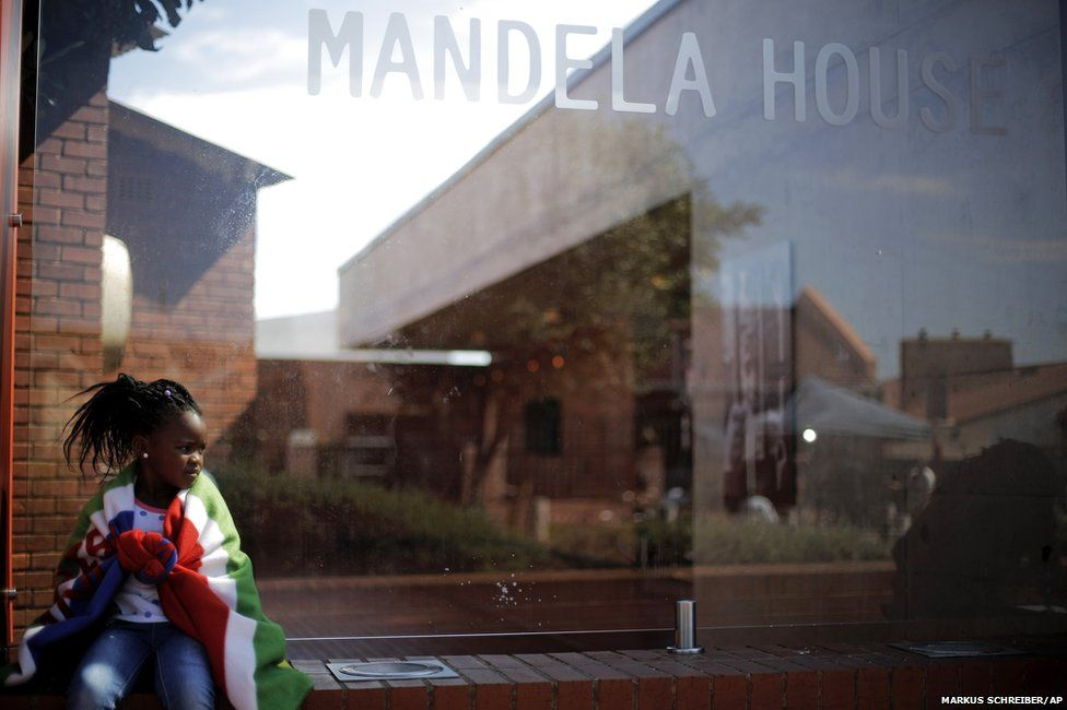 A girl sits outside the Mandela House Museum in the Soweto