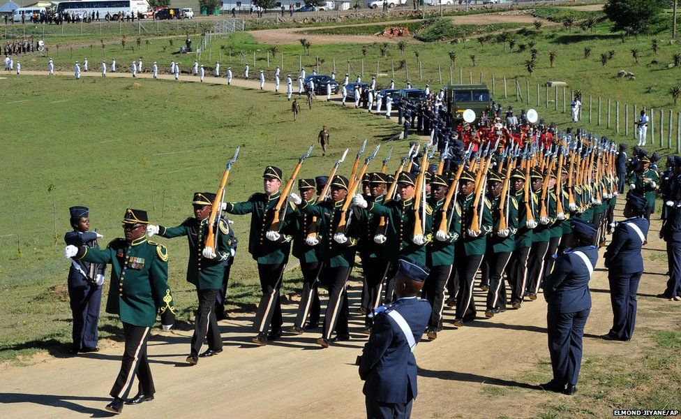 The casket of Nelson Mandela is brought in a military parade on a gun carriage from the family home to the funeral tent