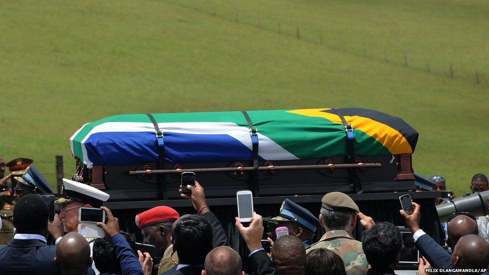 People take photographs of the casket