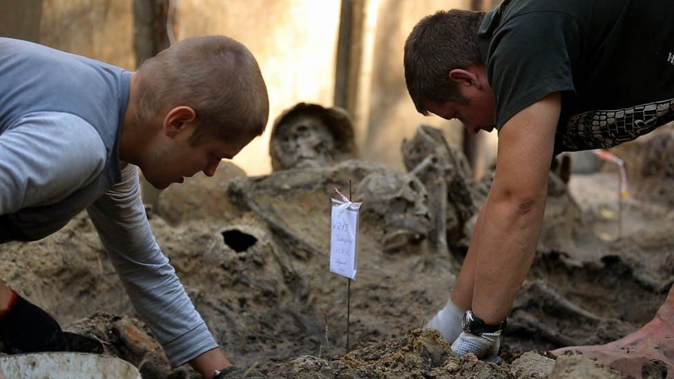 Diggers at a mass grave