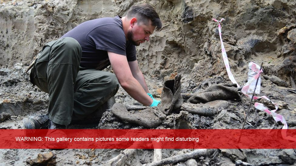 Man digging in mass grave
