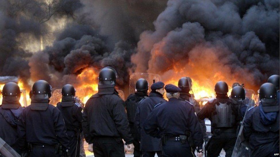 Bosnian policemen in front of a fire in Sarajevo (7 February 2014)