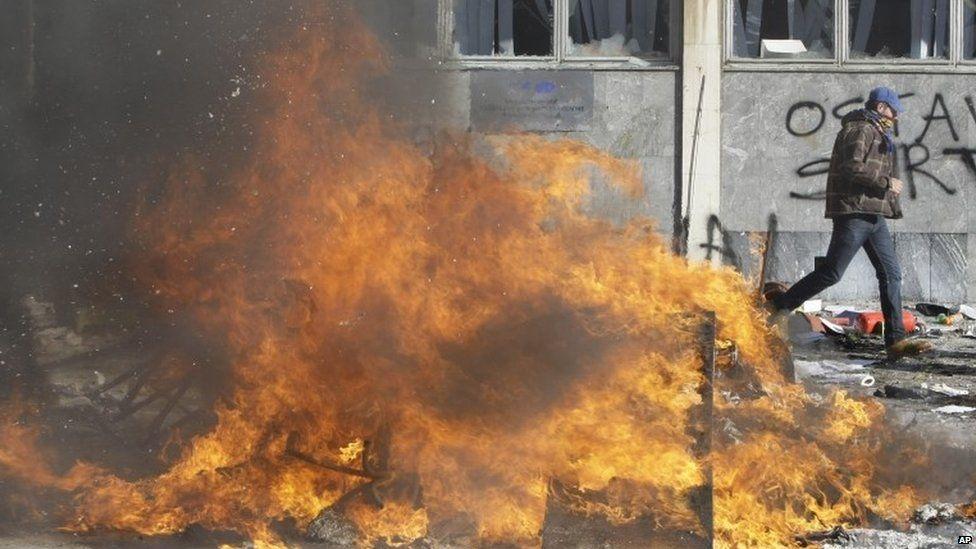 Man walks past a fire in Tuzla (7 February 2014)