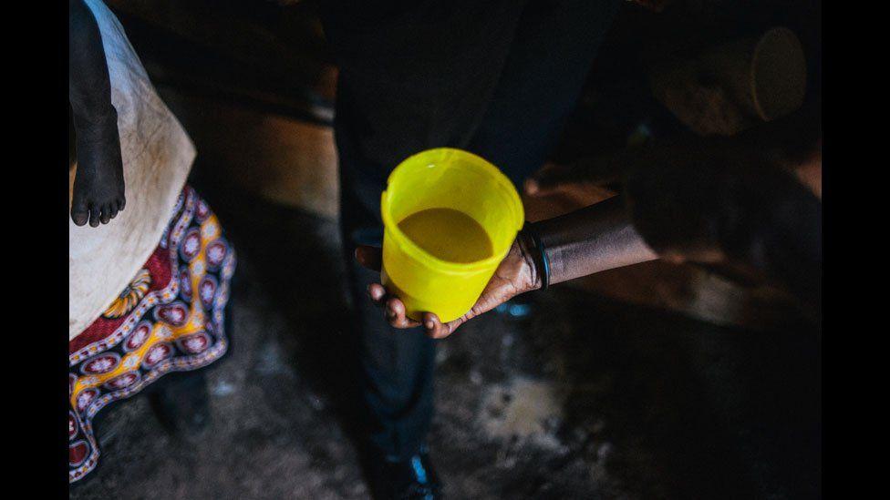 A yellow plastic beaker of busaa, Kenya