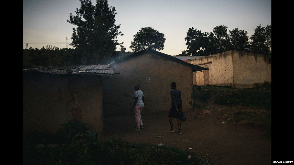 Village women heading towards a brewers den in western Kenya on a Sunday evening