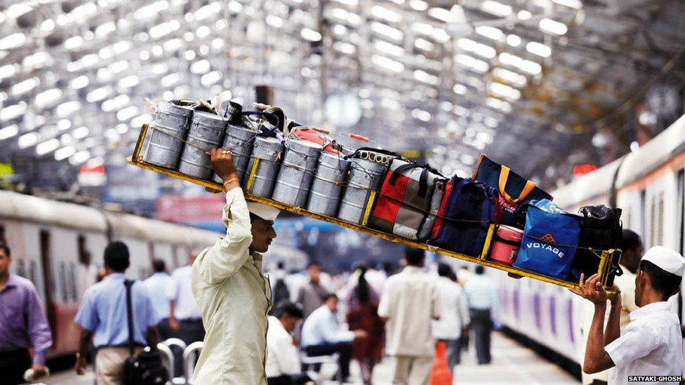 Two porters carry a tray of tiffin boxes onto a train in Mumbai