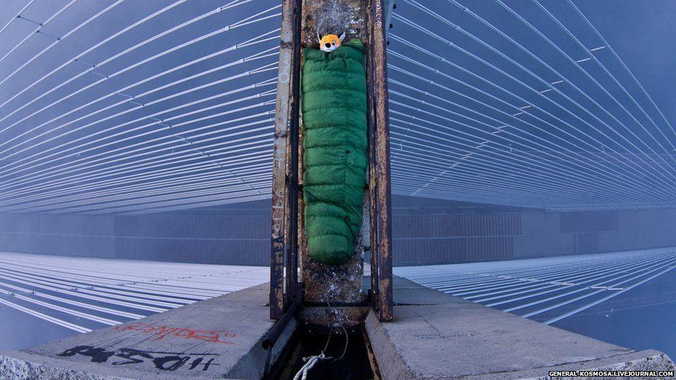 Explorer in a sleeping bag on top of a bridge.