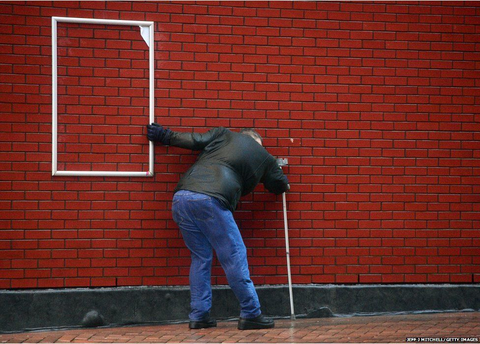 A man struggles in the high winds at Blackpool promenade