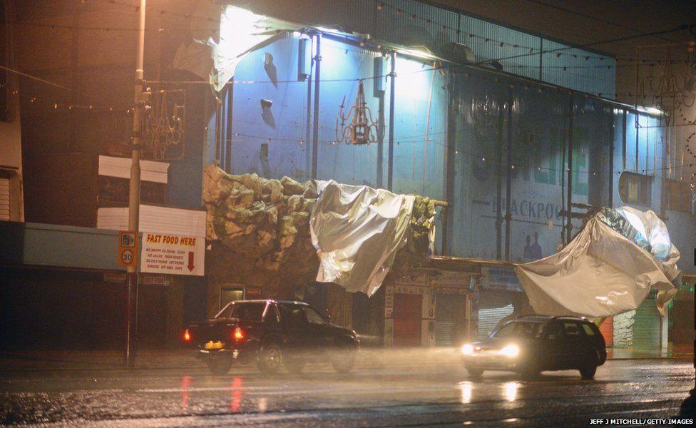 Traffic makes its way past a damaged building at Blackpool Promenade