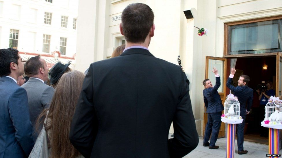 Phil Robathan (left) and James Preston throw the bouquet following their wedding ceremony in Brighton