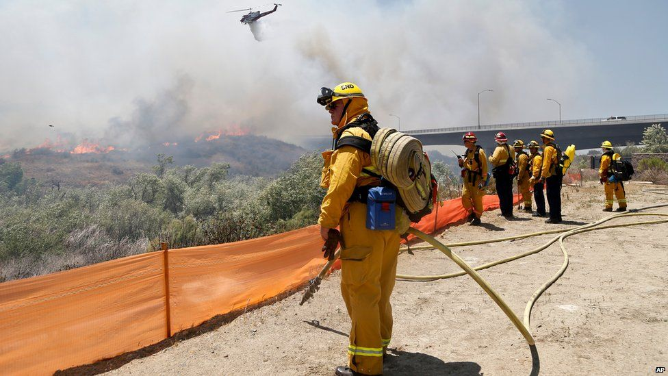 Firefighters watch from a ridge as a helicopter drops retardant on a wildfire in San Diego