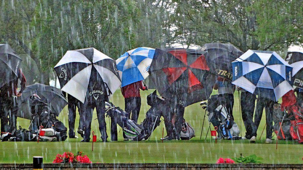 Golfers standing in the rain
