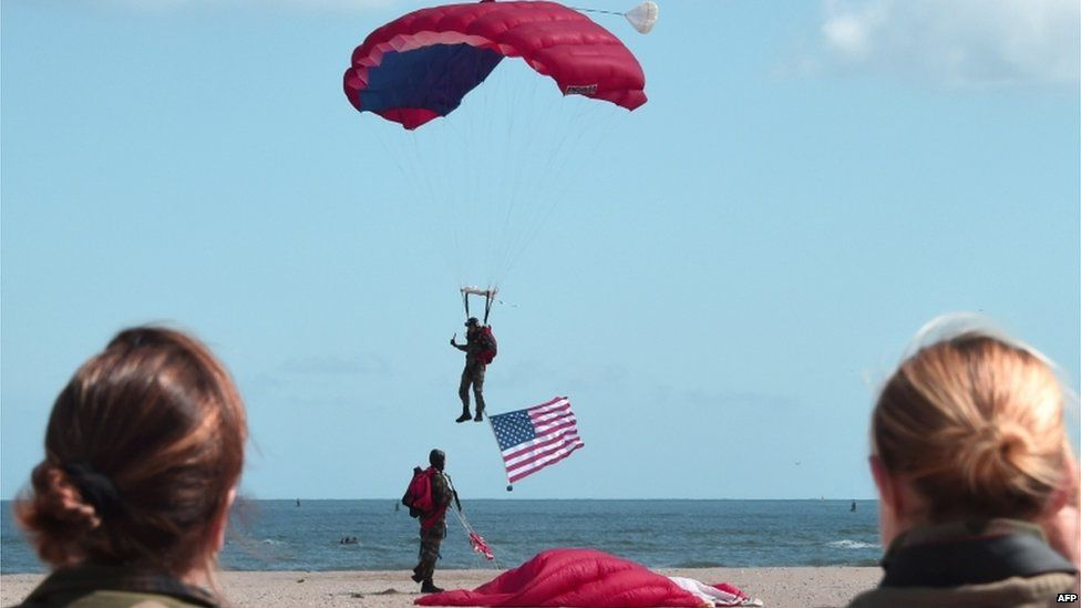A French paratrooper carrying a US flag landed on Sword beach in Ouistreham