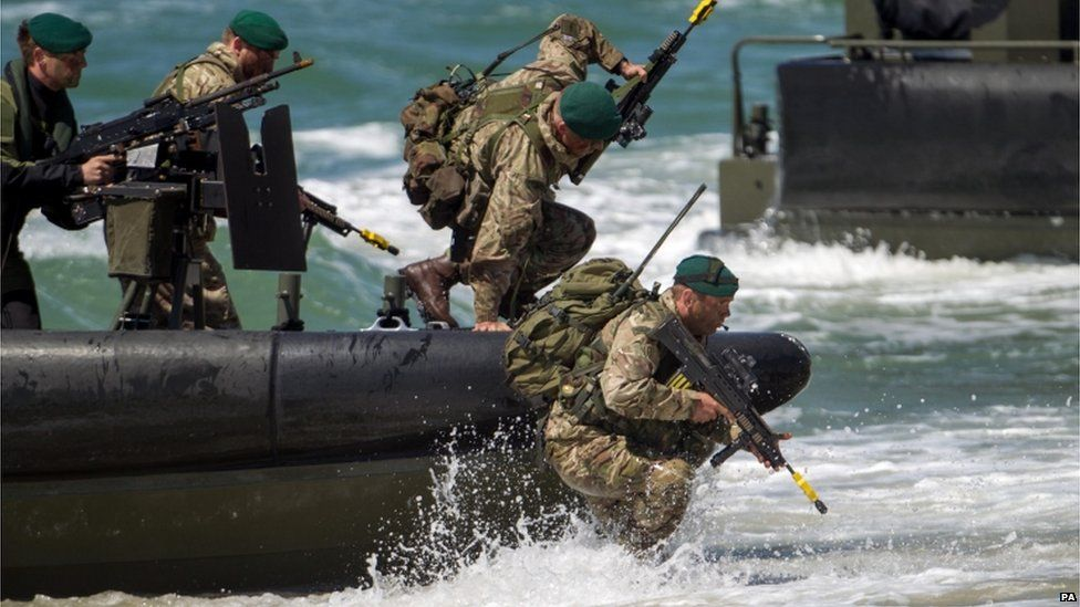 Troops jumping off a boat on to a beach