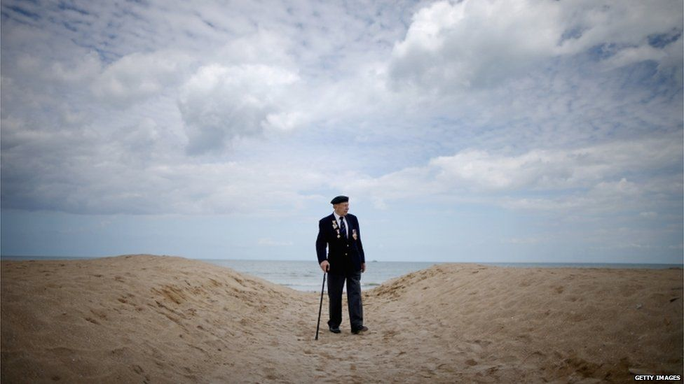 A British veteran walking alone on a beach