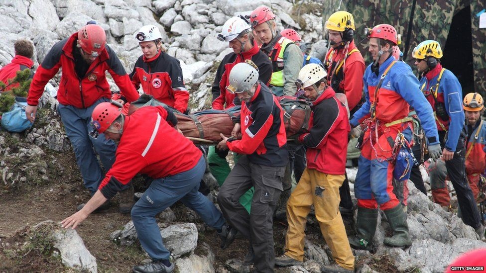 Stretcher carrying injured caver brought to surface.