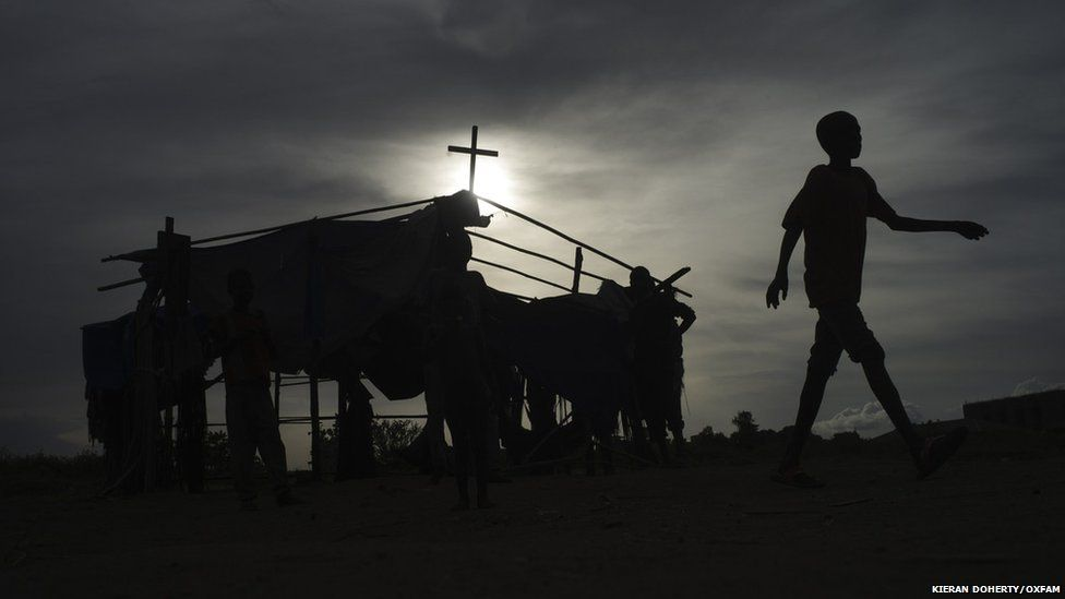 A boy walking past a ramshackle church in the the community of St Mary in Juba, South Sudan