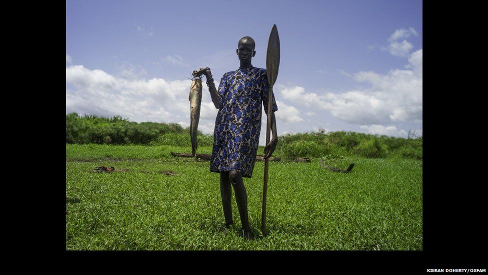 A fisherman poses with his fish on the River Nile in Mingkamen in Lakes State, South Sudan