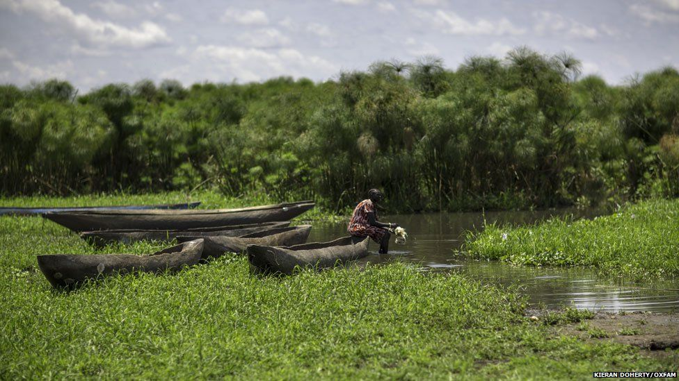 A fisherman sits on his canoe on the Nile, in Mingkaman, South Sudan.
