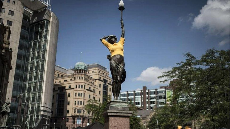 """A statue, draped with a yellow cloth in reference of the Tour de France overall leader""""s yellow jersey,"""
