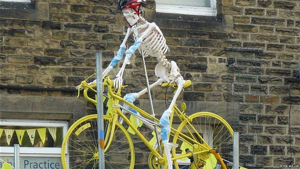 Skeleton on a yellow bicycle.