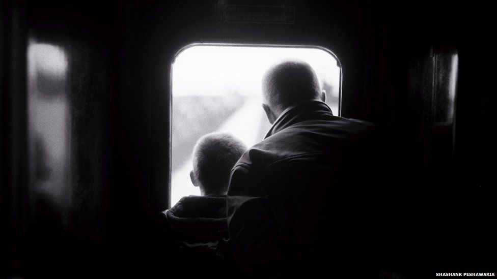 Two people look out of the window the train