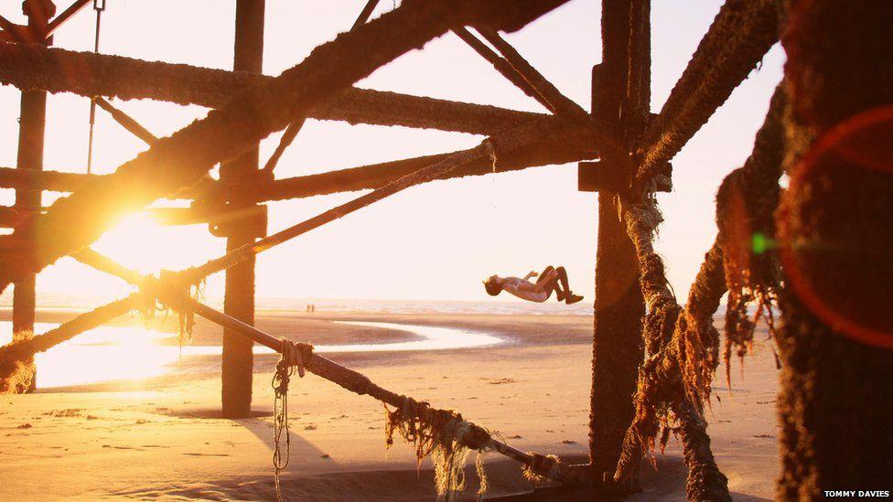 Boy doing a back flip during golden hour on Blackpool beach