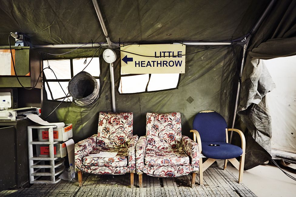 """Armchairs and a sign that reads """"Little Heathrow""""."""