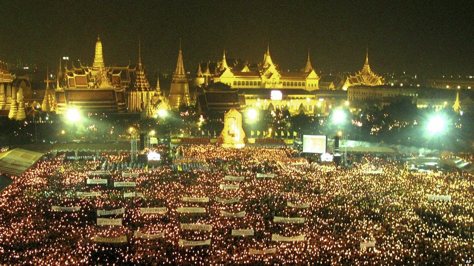 Thai people light the candles on the Royal Grounds, outside the Grand Palace