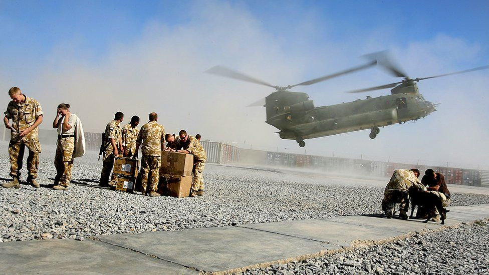 British soldiers from 16 Air Assault Brigade turn their heads as a Chinook lands on the helicopter pad at the Provincial Reconstruction Team base at Lashkar Gah in May 2006
