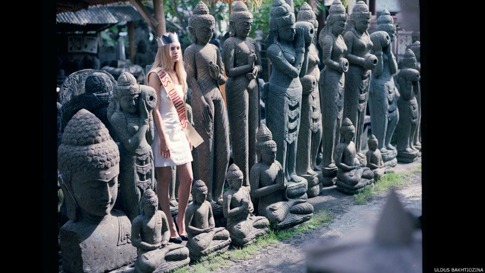 Women dressed as 'Miss Uniqueness' lined up among stone statues