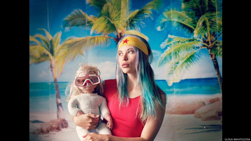Woman holding baby with a snorkel mask on