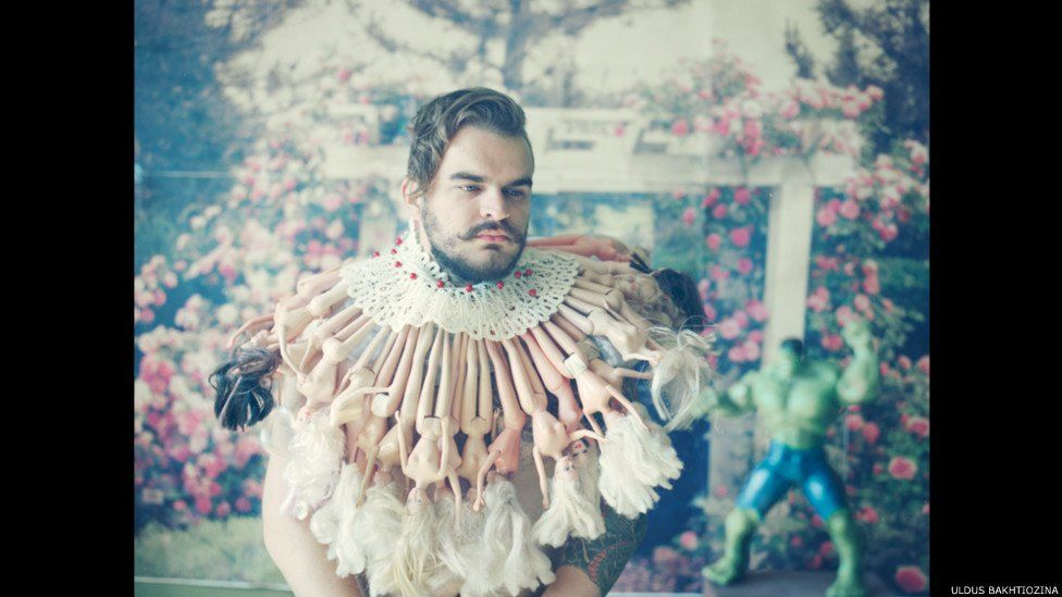 Man with neck ruff made from barbie dolls