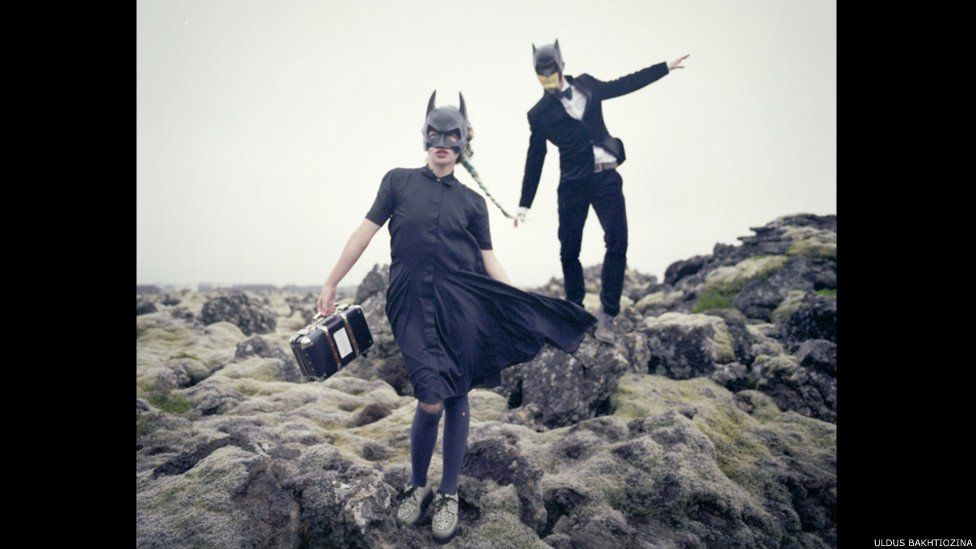 Woman and man with batman helmets on and a radio stereo