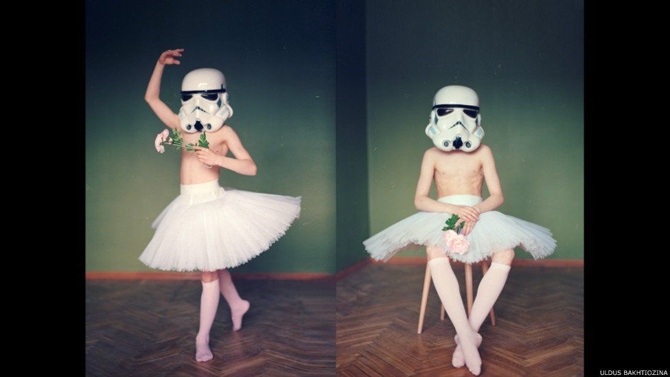 Boy with ballet skirt on and helmet