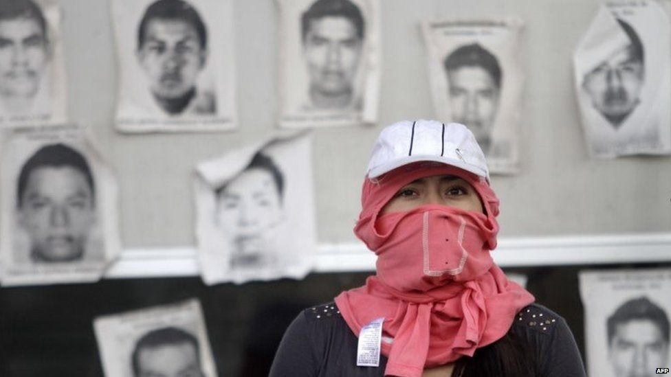 A hooded student is seen in front of the portraits of some of the 43 missing students at the tollbooths on the Chilpancingo-Acapulco highway on 12 November, 2014.