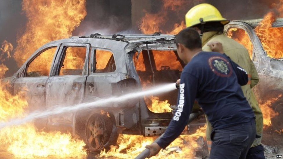 Firefighters try to extinguish the fire on vehicles set ablaze by protesters in Chilpancingo on 12 November, 2014