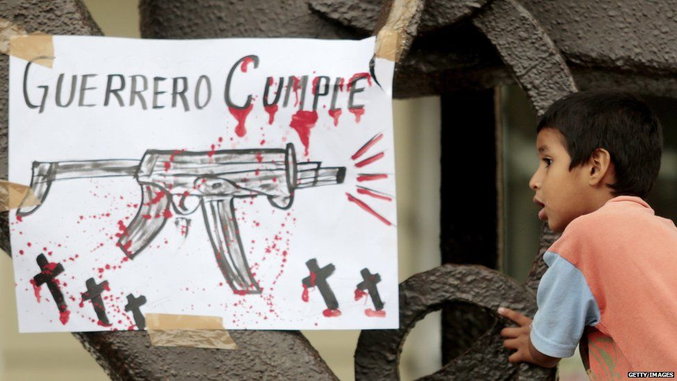 """A child is seen next to a sign reading """"Guerrero delivers"""" during a protest of teachers in demand of justice for the deaths of six people including students of Ayotzinapa and football players of the team 'Los Avispones' in Chilpancingo, Guerrero state, Mexico, on September 27, 2014."""