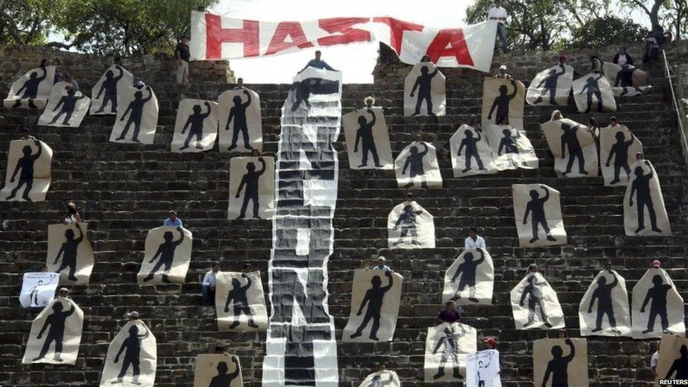 Activists hold painted silhouettes representing the 43 missing students, while performing a symbolic blockade of a pyramid at the archaeological site of Monte Alban in Oaxaca on 12 November, 2014