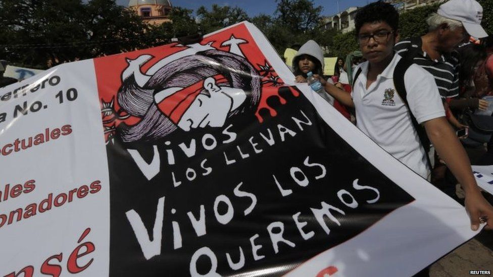 """A student holds a banner which reads """"They took them alive, we want them back alive"""" during a protest in support of missing students in Iguala on 11 November, 2014"""