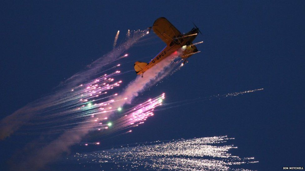 Fireworks being launched by a plane in flight, taken during the dusk display at the Bournemouth Air Show