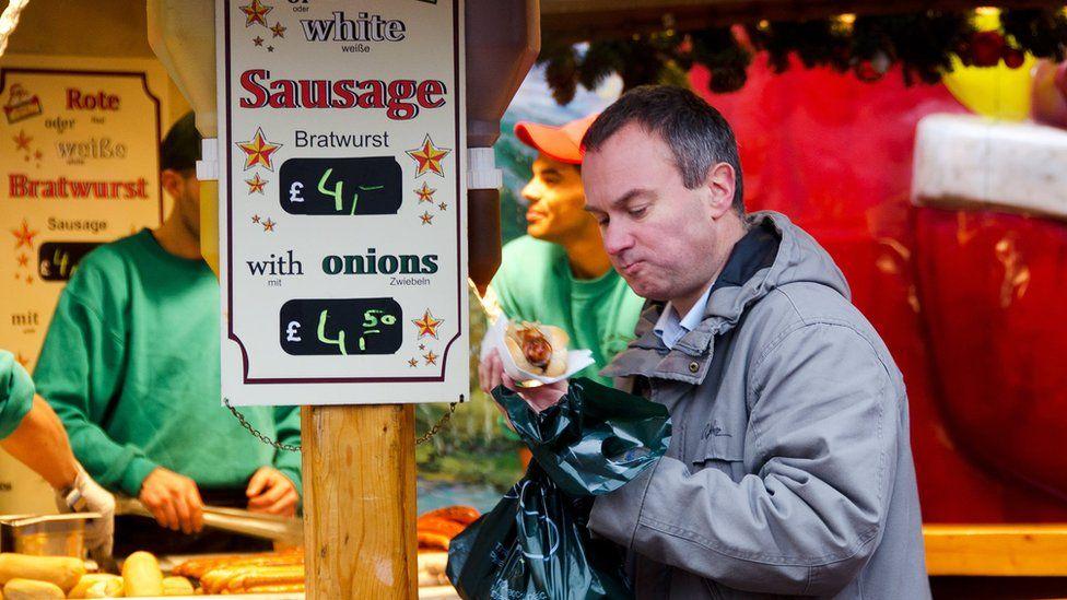 A man buys a bratwurst at the Christmas market